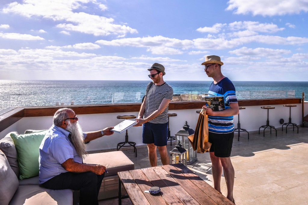 Famed seafood restaurateur Uri Jeremias chats with vacationers. Photo: Aviram Valdman / The Tower