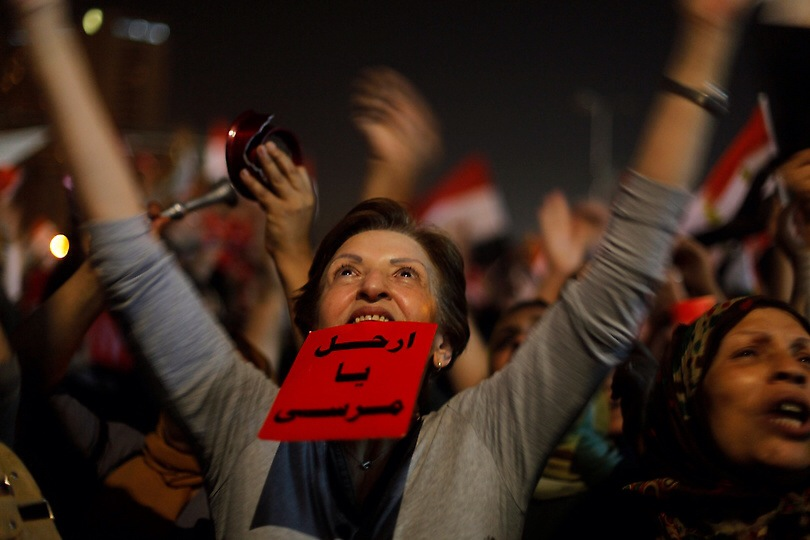 "An Egyptian protester holds a red card with Arabic that reads: ""Morsi: leave."" June 26, 2013. Photo: Amr Nabil/AP/Flickr"