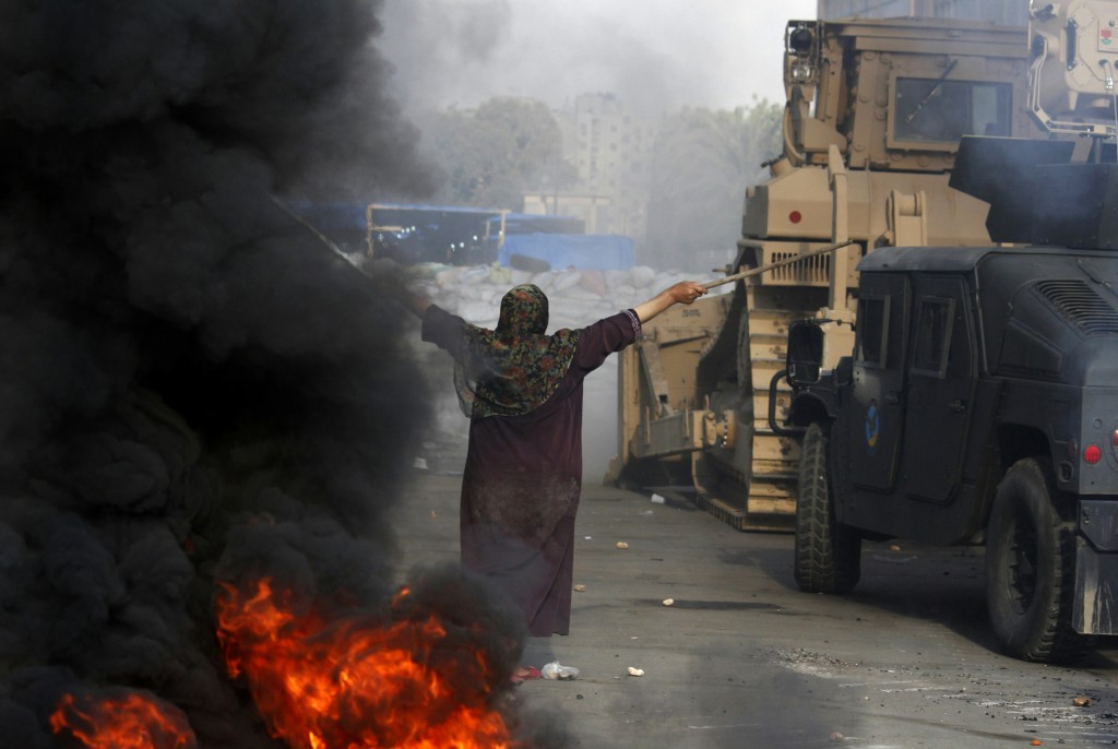 An Egyptian woman tries to stop a military bulldozer from going forward during clashes that broke out as Egyptian security forces moved in to disperse supporters of Egypt's deposed president Mohamed Morsi in a huge protest camp near Rabaa al-Adawiya mosque in eastern Cairo on August 14, 2013. The operation began shortly after dawn when security forces surrounded the sprawling Rabaa al-Adawiya camp in east Cairo and a similar one at Al-Nahda square, in the centre of the capital, launching a long-threatened crackdown that left dozens dead. Photo: AFP/Mohammed Abdel Moneim / flickr