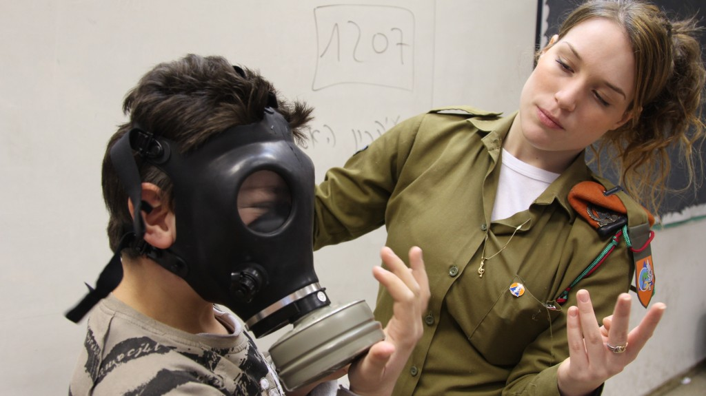 An IDF instructer teaches a child how to put on a gas mask in Holon. Photo: Israel Defense Forces / flickr