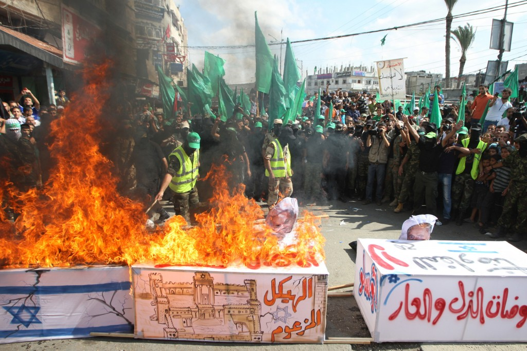 Hamas militants burn a coffin draped in an Israeli flag, during a rally marking the 13th anniversary of Second Intifada', in central Gaza Strip, 27 September 2013. Photo: Abed Rahim Khatib/Flash90
