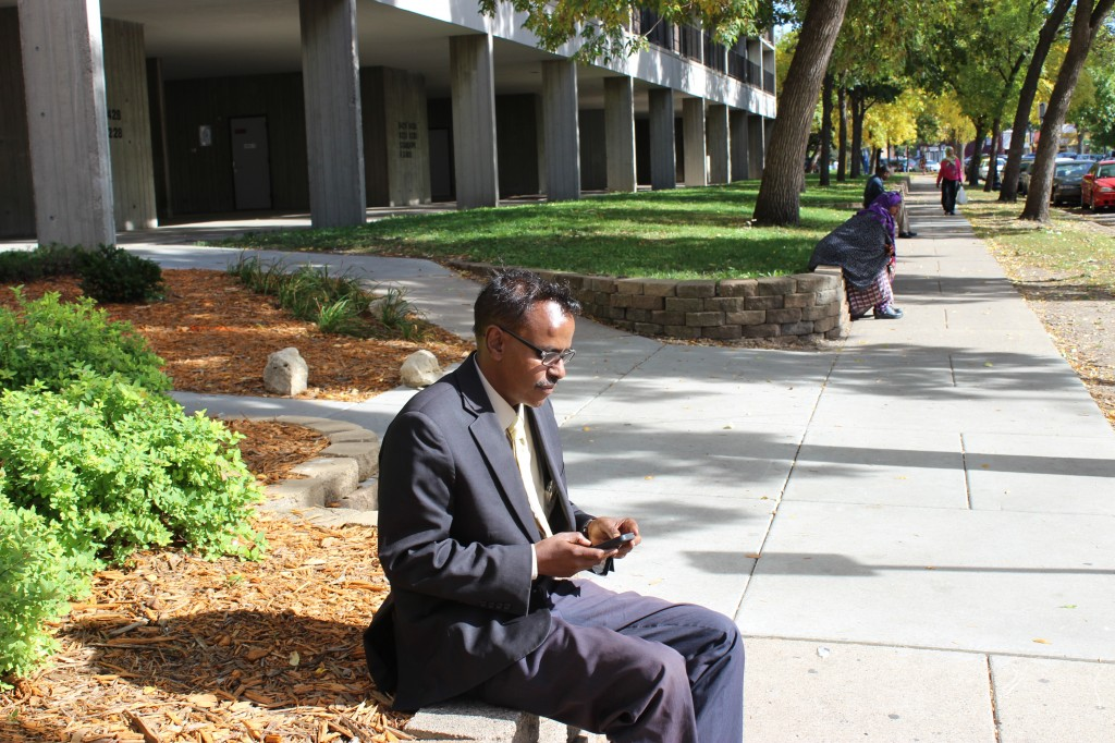 Abdirizak Bihi checks his email and text messages outside Riverside Plaza. Photo: Aiden Pink / The Tower