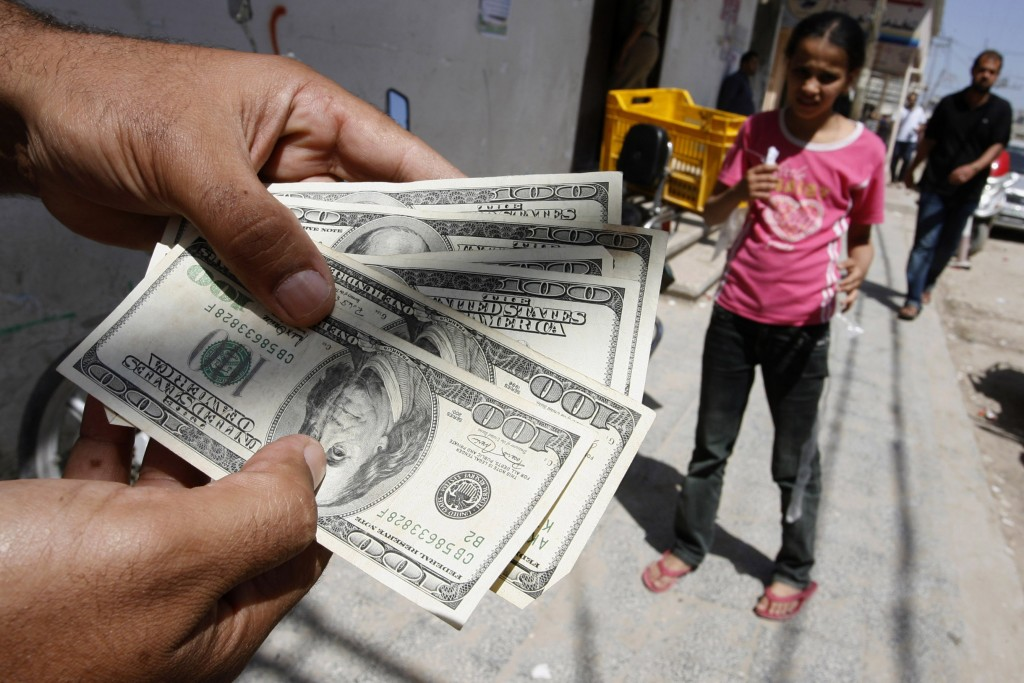 Palestinian man employed by the authority of Mahmoud Abbas' Fatah displays the money after withdrawn by ATM at the Bank of Palestine in Rafah, southern Gaza Strip on June 8, 2012, Photo Abed Rahim Khatib / Flash 90