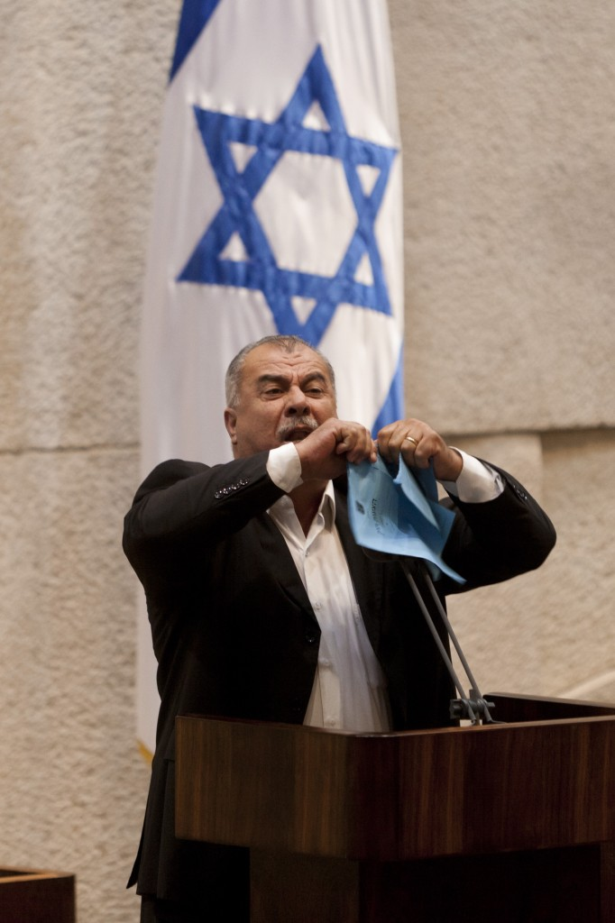 Knesset Member Mohammad Barakeh of the Hadash party tears the Prawer Plan during a plenum meeting in the Knesset, in Jerusalem, June 24, 2013. Arab Knesset members left the plenum Monday evening in protest. Photo: Flash 90