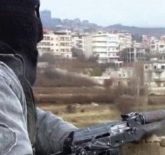 A member of the Free Syria Army with an assault rifle stands guard during a patrol in the western border town of Zabadani