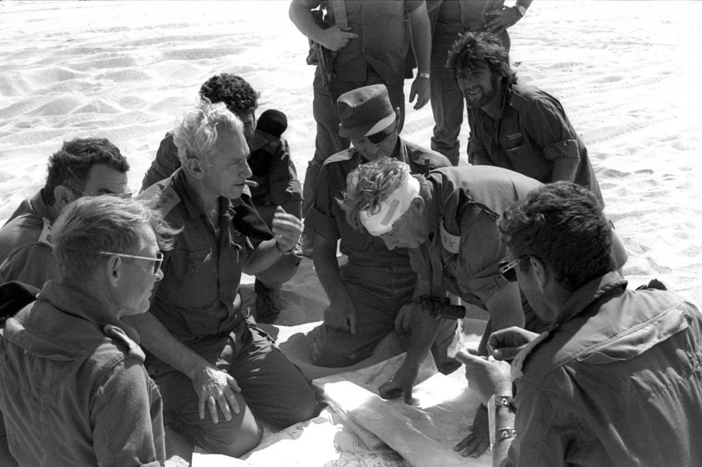 Haim Bar-Lev (center left), Moshe Dayan (with eyepatch), and Ariel Sharon (with head bandage) consult plans during the Yom Kippur War. Photo: Yossi Greenberg / GPO / Flash90