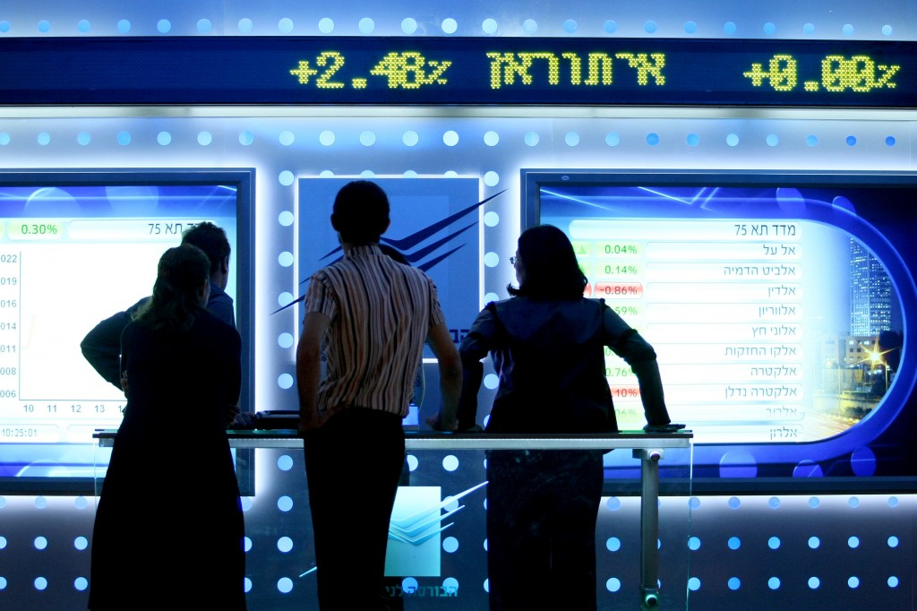 People watch a board showing stock fluctuations at the Tel Aviv stock exchange. Photo: Moshe Shai / Flash90