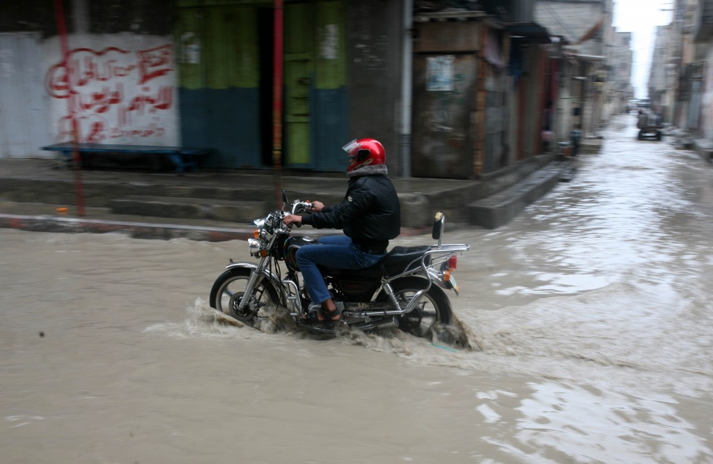 A Palestinian man rides his a bike through a flood in Gaza City. Photo: Mohammed Othman / Flash90