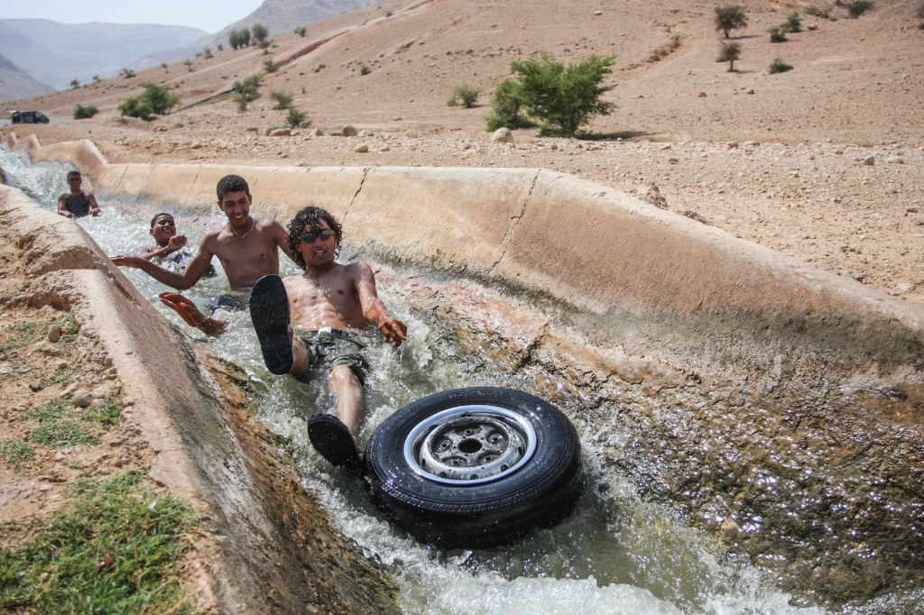 Palestinians playing in a running stream of channeled irrigation water to cool off, on a hot summer day in the West Bank city of Jericho, where the temperatures soared to 40 degrees. Photo: Issam Rimawi / Flash90