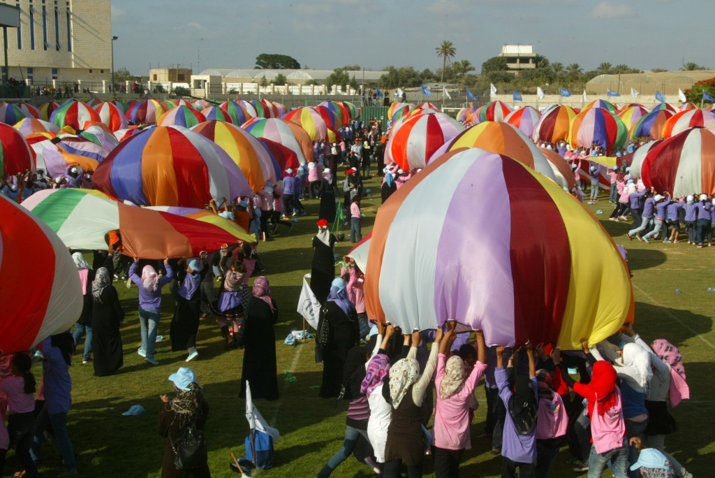Palestinian children perform with parachutes during summer camp activities supervised by UNRWA in Khan Yunis in the southern Gaza Strip, June 30, 2011. They attempted to break the Guinness world record for most parachutes bounced simultaneously. Photo by Abed Rahim Khatib / Flash90