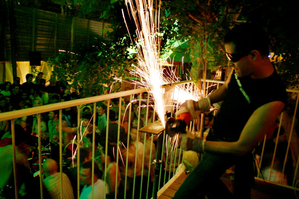 A man uses a buzzsaw to create sparks at the opening party for Blend, a nightclub in Tel Aviv. Photo: Melanie Fidler / Flash90