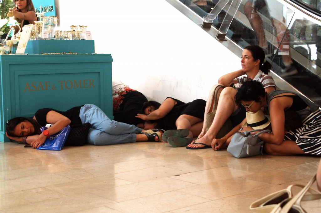 Israelis take cover at the Dizengoff Center mall in Tel Aviv as sirens alert to incoming rockets from Gaza. Photo: Roni Schutzer / Flash90