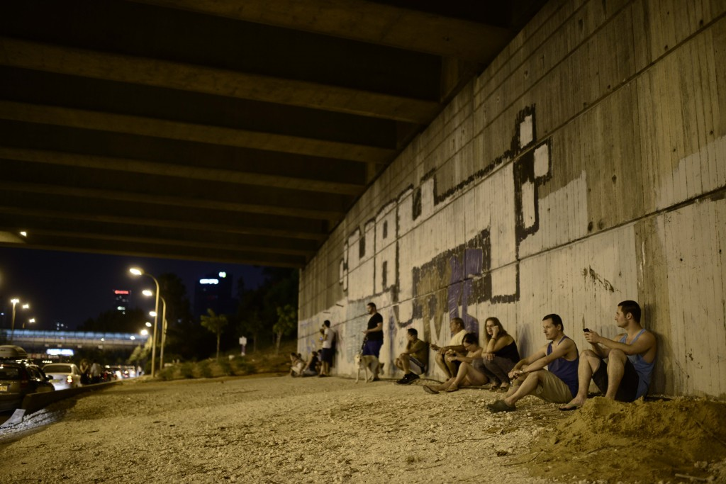 Israelis in Tel Aviv take cover as a siren warns of incoming rockets. Photo: Tomer Neuberg / Flash90