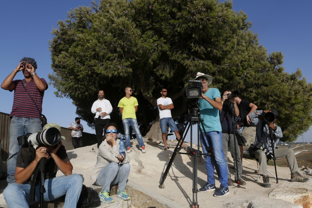 Israelis and journalists stand on a hill overlooking the Gaza Strip observing military activites on the sixth day of Operation Protective Edge, July 13, 2014. Photo: Miriam Alster / Flash90