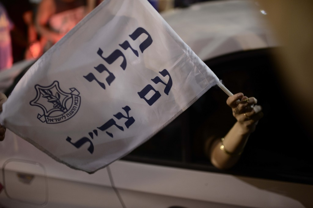 "A woman holds a flag reading ""All of us are with the IDF: as she drives by a demonstration in Rabin Square in Tel Aviv, July 26, 2014. Photo: Tomer Neuberg / Flash90"