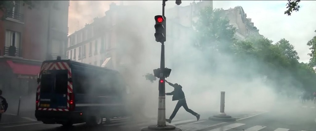 A protester launches a flower pot on a truck while the street is full of tear gas outside the Synagogue de la Roquette. Photo: RuptlyTV / YouTube