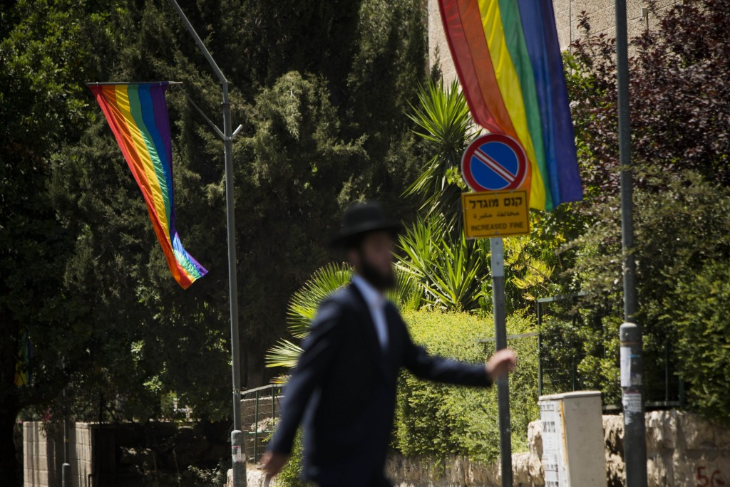 An ultra-Orthodox Jewish man passes by rainbow flags hung up by the Jerusalem municipality ahead of the 2013 Jerusalem Gay Pride Parade. Photo: Yonatan Sindel / Flash90