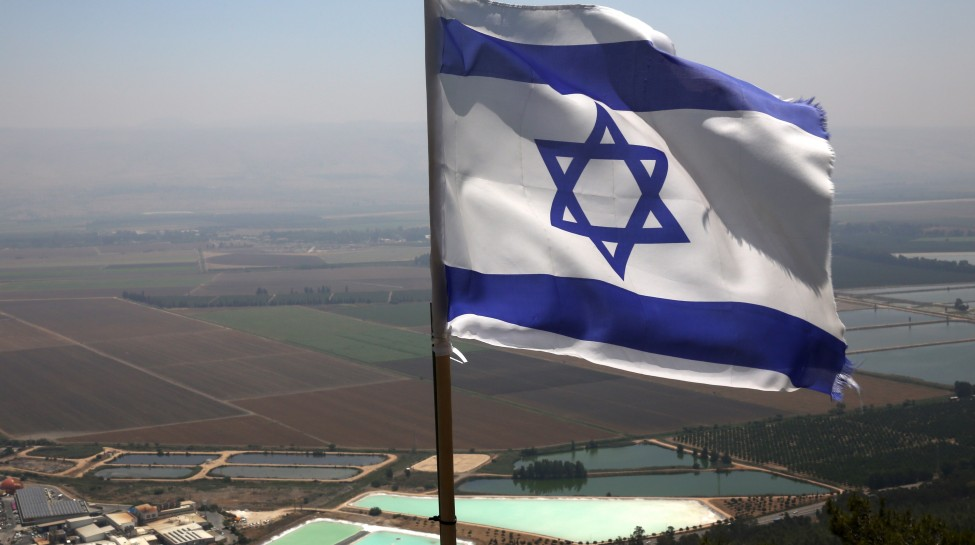 The Israeli flag waves in the wind above the northern Israeli city of Kiryat Shmona, August 13, 2014. Photo: Nati Shohat / Flash90
