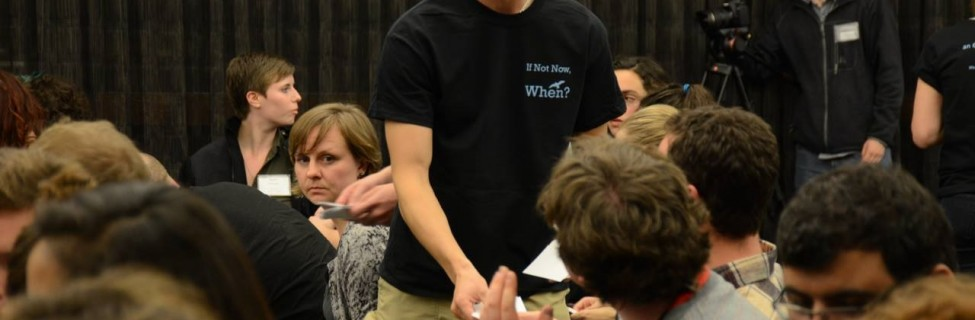 An Open Hillel member hands out materials at a plenary session. Photo: Gili Getz