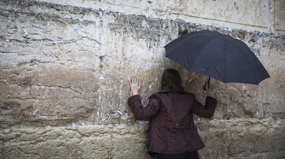A Jewish woman prays at the Western Wall in Jerusalem's Old City while holding an umbrella during heavy rainfall, November 16, 2014. Photo: Hadas Parush / Flash90