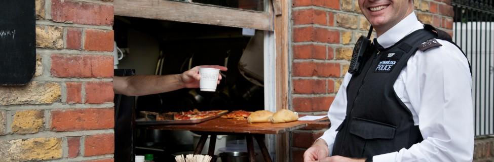 A British policeman buys lunch at Columbia Market, London. Photo: Jorge Royan / Wikimedia