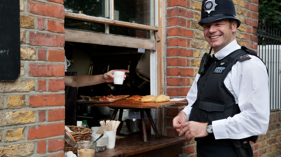 A British policeman buys lunch at Columbia Market, London. Photo: Jorge Royan / Wikimedia