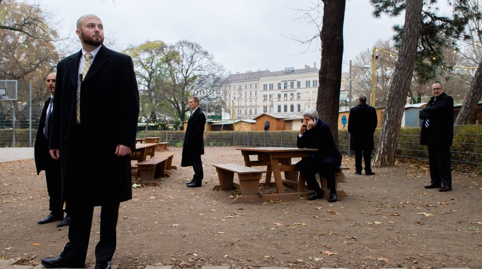 U.S. Secretary of State John Kerry, ringed by security guards, speaks with Canadian Foreign Minister John Baird about the status of nuclear program negotiations with Iranian officials as he sits in a park at the scene of the talks, Vienna, Austria, on November 22, 2014. Photo: U.S. Department of State / flickr
