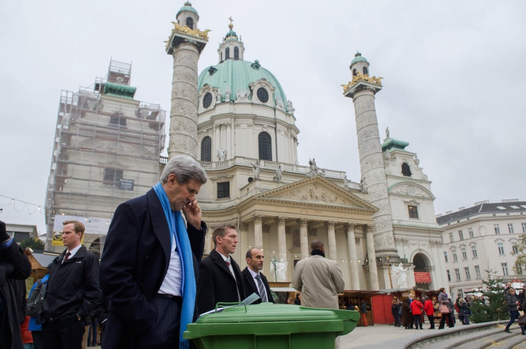 U.S. Secretary of State John Kerry balances his notes on a recycling bin as he speaks with Turkish Foreign Minister Mevlut Cavusoglu about the status of nuclear program negotiations with Iranian officials as he takes a walk at the scene of the talks, Vienna, Austria, on November 22, 2014. Photo: U.S. Department of State / flickr