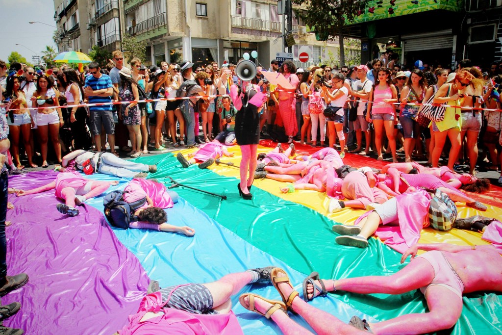 "During the 2013 Tel Aviv Pride Parade, the anarcho-queer collective ""Mashpritzot"" (""Squirters"") held a die-in to protest Israeli ""pinkwashing"" and the priorities of the city-sponsored LGBT center. Photo: Tmagen / Wikimedia"