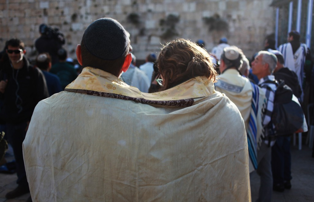 A woman and a man attempt to pray together at the Western Wall. Photo: Tal King / flickr