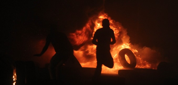 Palestinian men burn tires during clashes with Israeli border police at theQalandiya checkpoint, between Jerusalem and Ramallah, late on July 24, 2014, following a massive march attended by 10,000 Palestinian protesters against Israel's military actions in the Gaza Strip. Photo: Issam Rimawi / Flash90