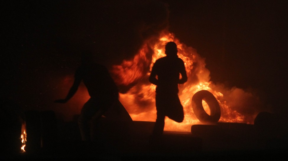 Palestinian men burn tires during clashes with Israeli border police at the Qalandiya checkpoint, between Jerusalem and Ramallah, late on July 24, 2014, following a massive march attended by 10,000 Palestinian protesters against Israel's military actions in the Gaza Strip. Photo: Issam Rimawi / Flash90