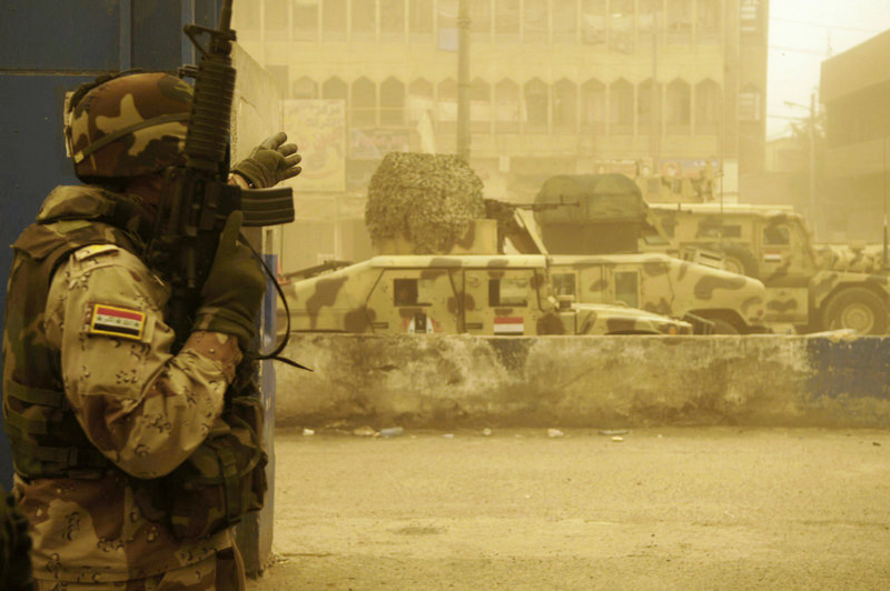 An Iraqi army soldier takes cover during a firefight against armed militiamen in the Sadr City district of Baghdad. Photo: Technical Sgt. Adrian Cadiz / U.S. Air Force / Wikimedia