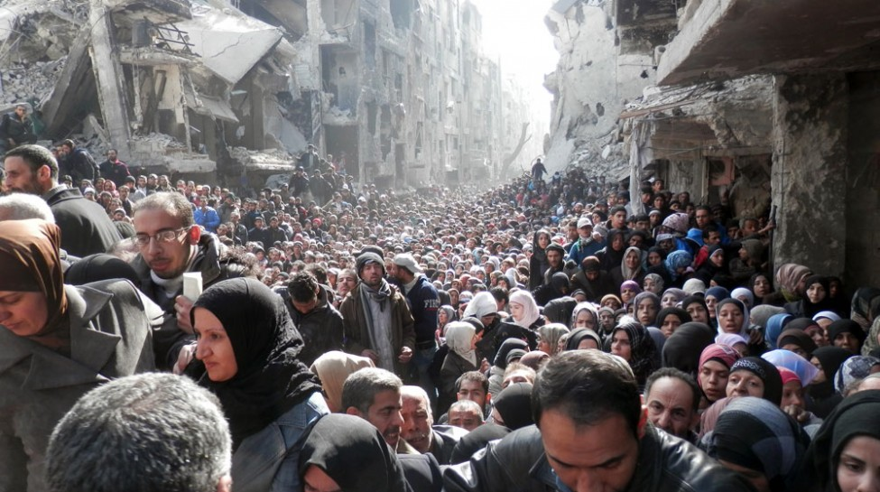 Residents of the Yarmouk refugee camp line up for aid distributed by UNRWA, February 2014. Photo: Rami Al Sayyed / UNRWA / flickr