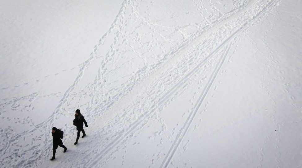 People cross a snow-covered field on a winter day in Stockholm. Photo: Miriam Alster / Flash90