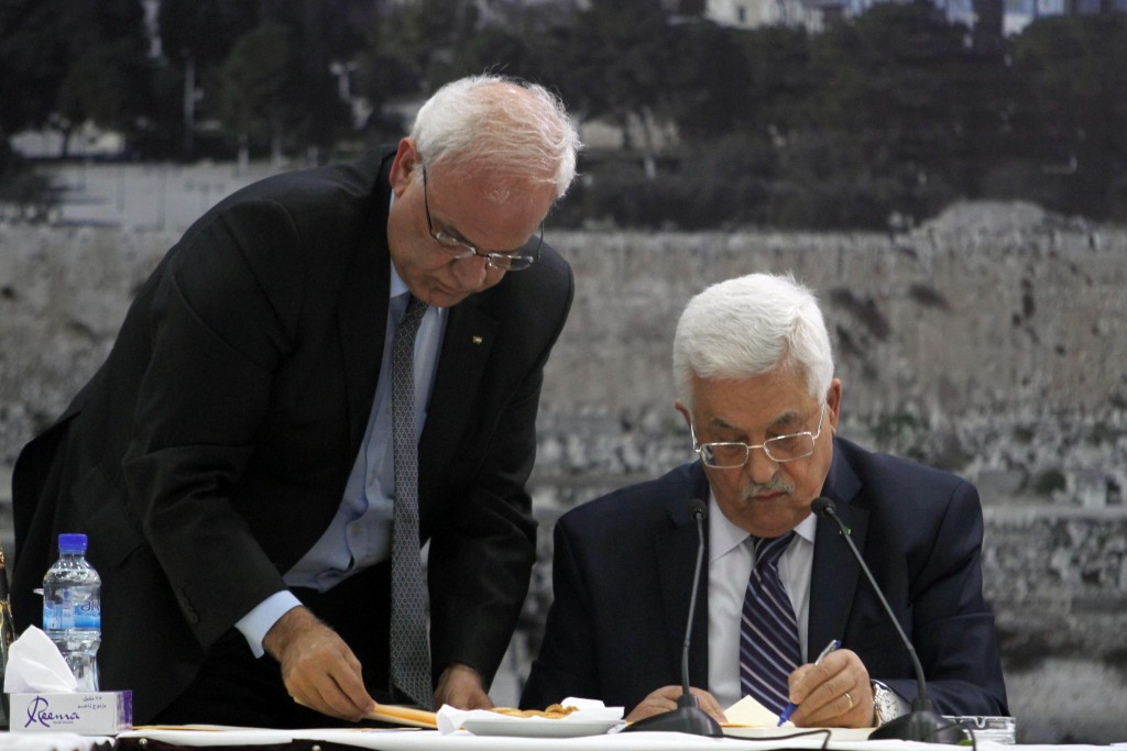 Palestinian Authority President Mahmoud Abbas (R)  signs applications to join 15 UN agencies as chief peace negotiator Saeb Erekat assists him, April 1, 2014. Photo: Issam Rimawi / Flash90