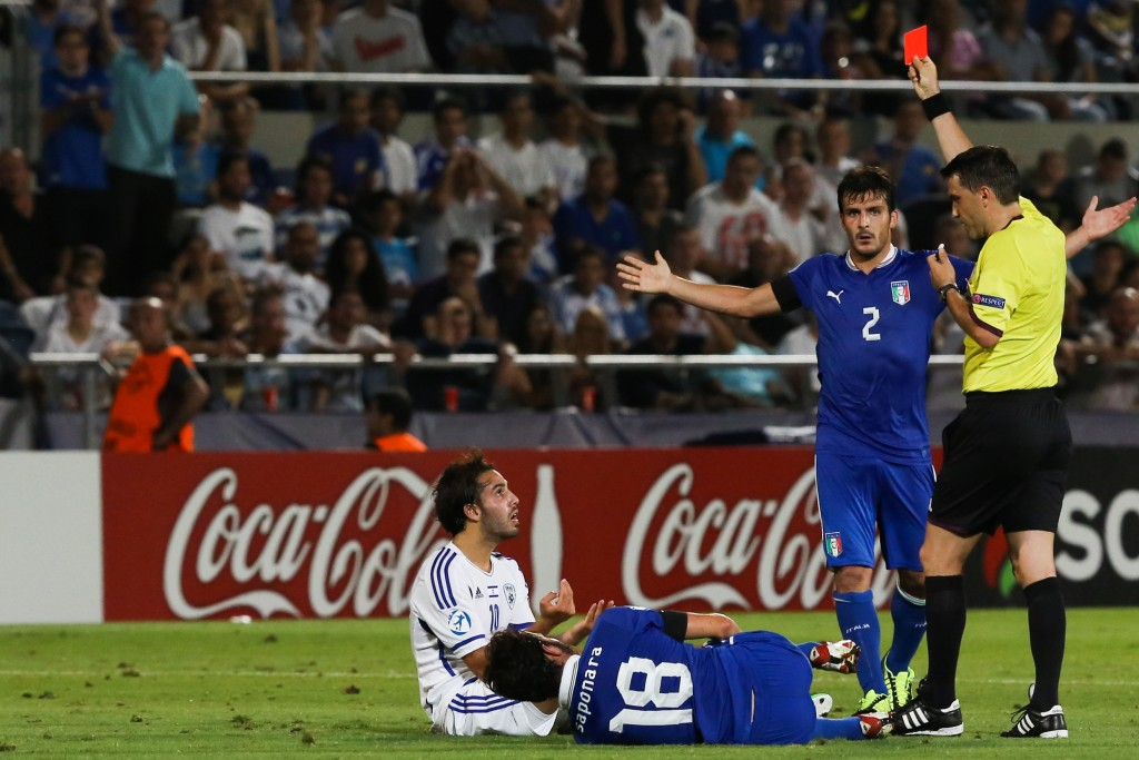 Israeli Eyal Golasa (in white) gets a red card during a UEFA European Under-21 Championships match between Israel and Italy at Bloomfield Stadium in Tel Aviv, June 8, 2013. Israeli teams cannot play against other teams in Asia due to an Arab and Muslim sports boycott, forcing them to play stronger European teams. Photo: Yonatan Sindel / Flash90