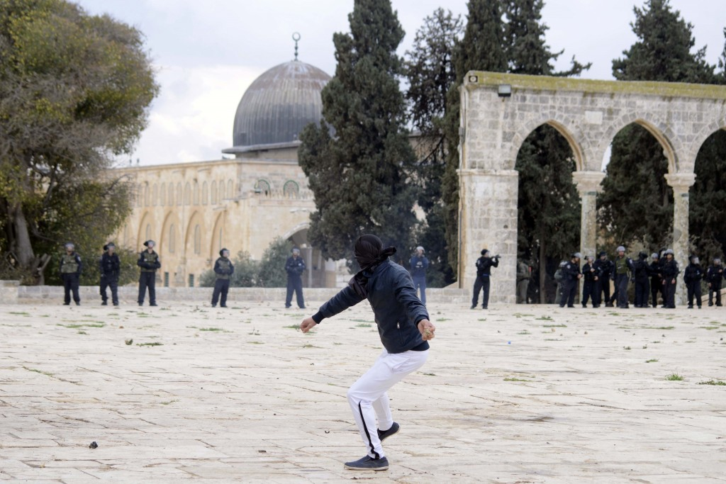 A Muslim boy throws stones at Israeli police during clashes following Friday prayers at Jerusalem's al-Aqsa mosque, December 6, 2013. Photo: Sliman Khader / Flash90