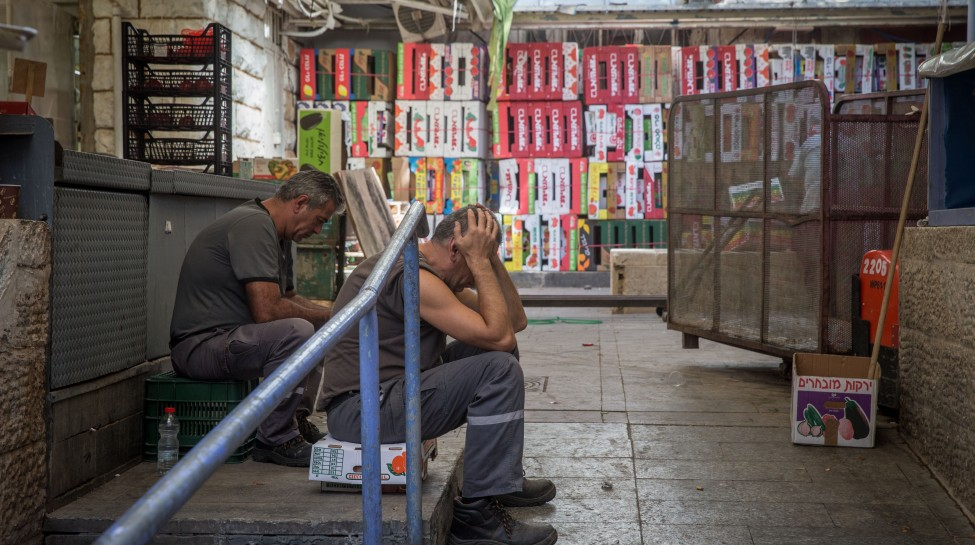 Workers sit in an alleyway at the nearly-empty Mahane Yehuda market in Jerusalem, October 15, 2015. Photo: Nati Shohat / Flash90