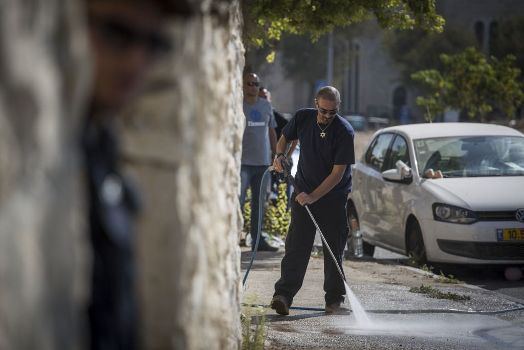A sanitation worker cleans up the scene of an attempted stabbing attack in Jerusalem, October 17, 2015. Police were called to check on a suspicious-looking Arab man in the neighborhood of Armon Hanatziv. When they came to check his ID, he pulled out a knife, injuring a policeman before being shot and killed. Photo: Hadas Parush / Flash90