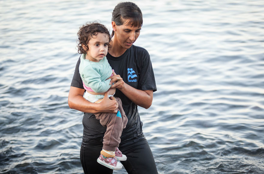Tali Shaltiel, an Israeli physician, taking a Syrian child from a dinghy that arrived at a beach on the Greek island of Lesbos. Photo: Boaz Arad/IsraAid