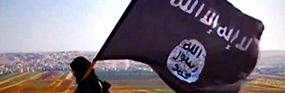 A member of Islamic State carries the group's flag. Photo: VOA / Wikimedia