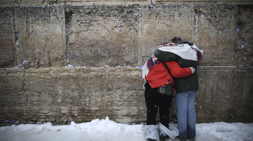 Worshipers pray amid snowfall at the Western Wall. Photo: Hadas Parush / Flash90