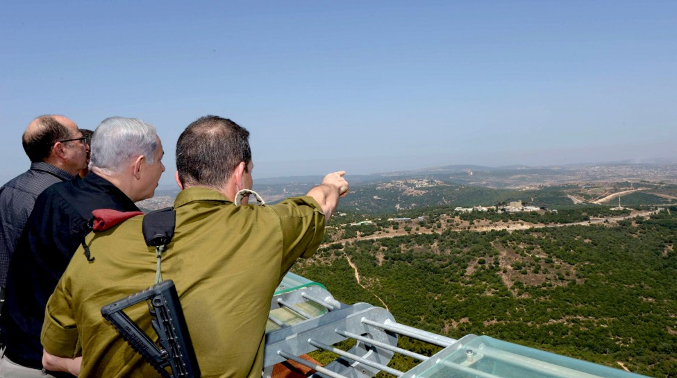 Israeli Prime Minister Benjamin Netanyahu (C) and Defense Minister Moshe Ya'alon (L) look out into Syria during a visit to the northern border, August 18, 2015. Photo: Amos Ben Gershom / GPO / Flash90