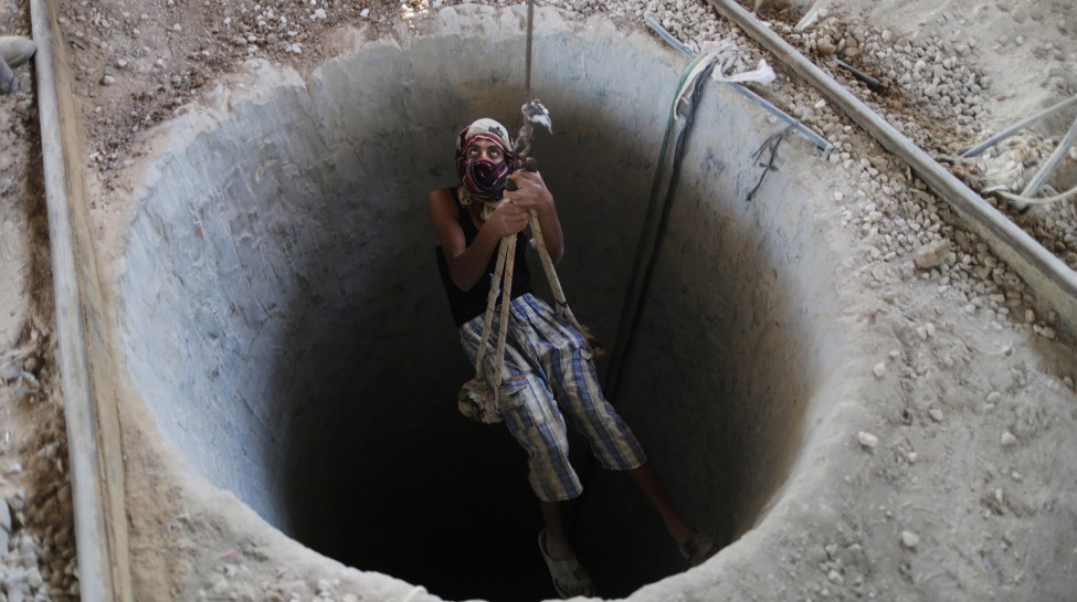A Palestinian man is lowered into a smuggling tunnel in Rafah near the border with Egypt, September 10, 2013. Photo: Wissam Nassar / Flash90