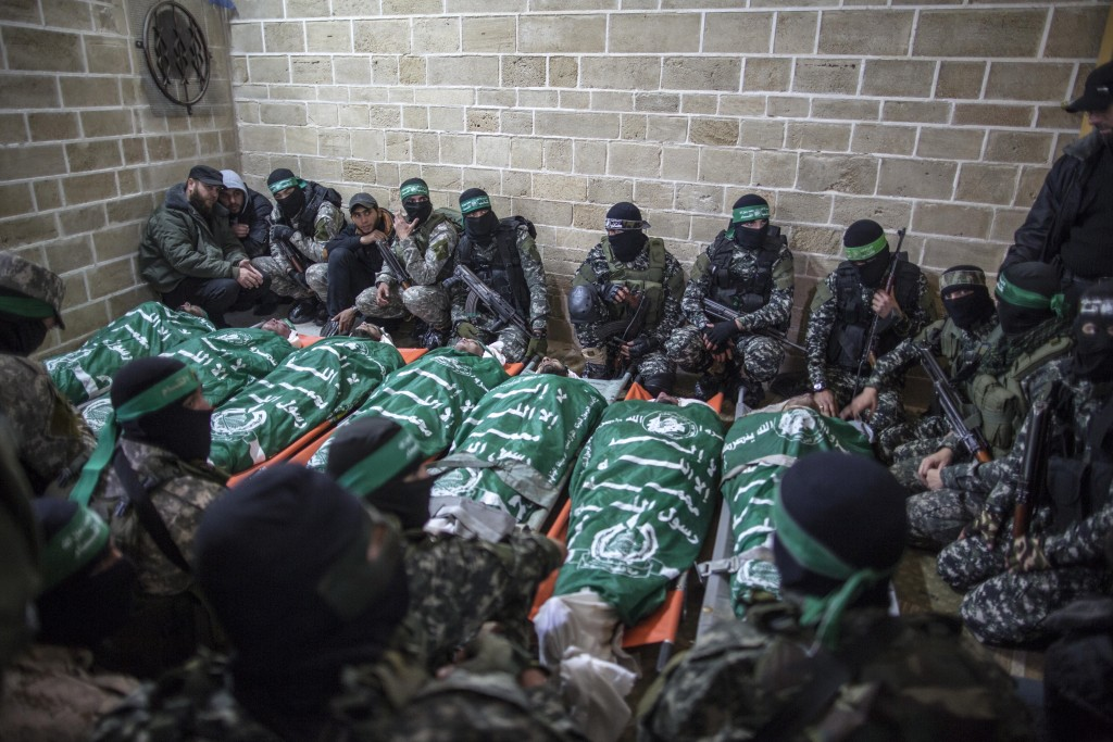Members of the Izz ad-Din al-Qassam Brigades, Hamas' militia, pray near the bodies of seven members who were killed while repairing a tunnel, January 29, 2016. Photo: Emad Nassar / Flash90
