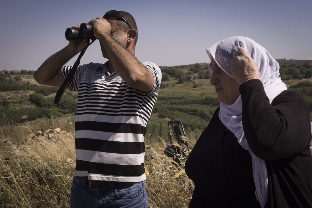 A Druze man and woman on the Israeli side of the Golan Heights watch the fighting taking place on the Syrian side, June 16, 2015. Photo: Basel Awidat / Flash90