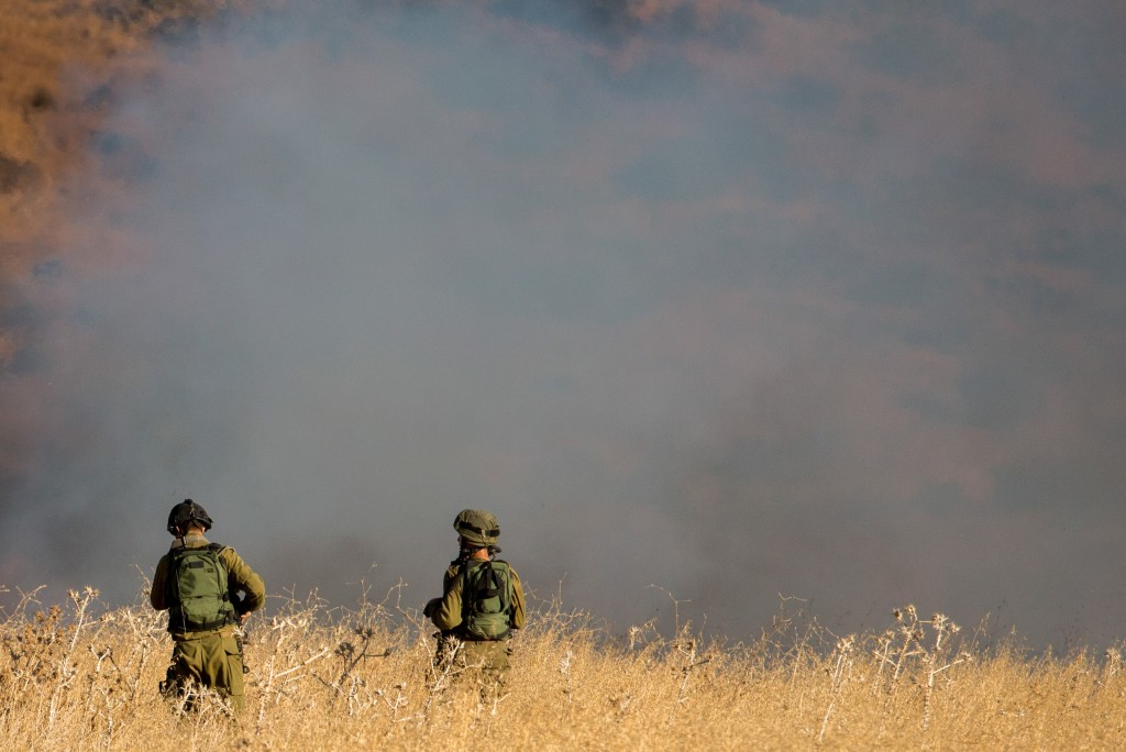 Israeli soldiers examine a fire caused by missiles fired from Syria that hit open areas in the Golan Heights, August 20, 2015. Photo: Basel Awidat / Flash90