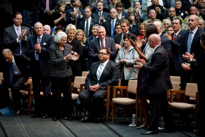 Daniel Hernandez receives a standing ovation at a memorial event dedicated to the victims of the Tucson shooting. First Lady Michelle Obama and Gabrielle Giffords' husband, astronaut Mark Kelly, stand next to him. Photo: Chuck Kennedy / White House / Wikimedia