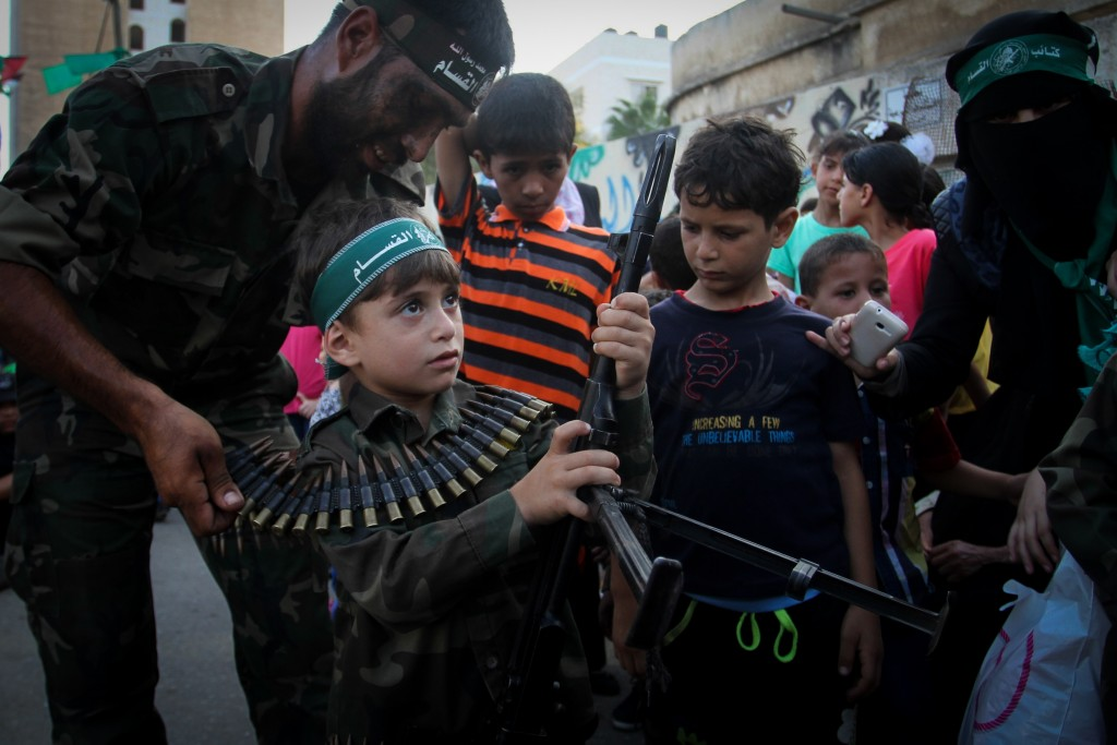 A Palestinian boy holds his father's weapon during a graduation ceremony as part of a military-style summer camp organized by Hamas, August 2015. Photo: Abed Rahim Khatib / Flash90